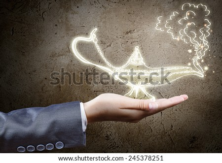 Close up of businessperson hand holding lamp in hand - stock photo