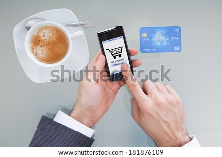 Close-up Of Businessperson Hand Holding Mobile Phone With Online Shopping Application - stock photo
