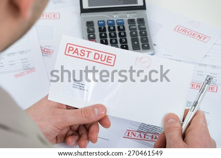 Close-up Of Businessperson Hand Holding Past Due Envelope - stock photo