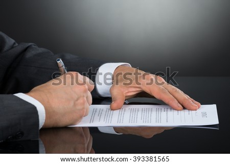 Close-up Of Businessperson Hand Signing Contract Paper With Pen At Desk