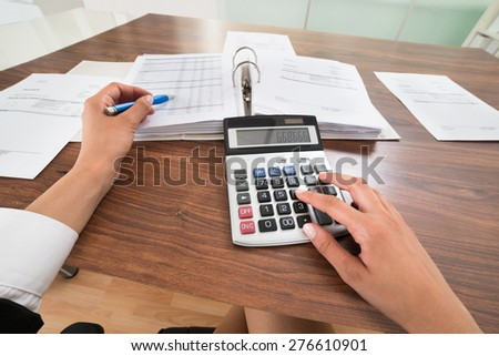 Close-up Of Businessperson Hands Calculating Bills With Calculator At Desk. Documents were created by photographer - stock photo