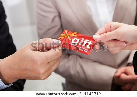 Close-up Of Businessperson Hands Giving Gift Card To Other Businessperson - stock photo