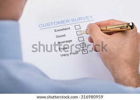 Close-up Of Businessperson Hands With Pen Marking On Customer Survey Form - stock photo