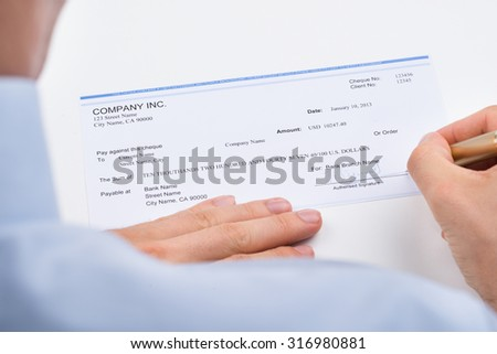 Close-up Of Businessperson Hands With Pen Signing Cheque - stock photo