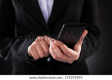 Close-up Of Businessperson Holding Black Cellphone Over Black Background - stock photo