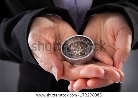 Close-up Of Businessperson Holding Compass In Hand - stock photo