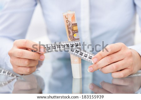 Close-up Of Businessperson Holding Measuring Tape Around An Euro Banknote - stock photo