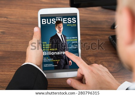 Close-up Of Businessperson Holding Mobile Phone With Business News On Screen - stock photo