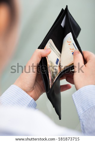 Close-up Of Businessperson Holding Open Wallet With Banknote - stock photo