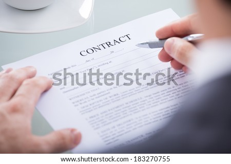 Close Up Of Businessperson Holding Pen On A Contract Paper - stock photo
