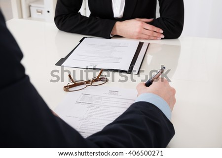 Close-up Of Businessperson Holding Pen Over Resume In Office - stock photo