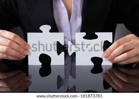 Close-up Of Businessperson Holding Two Puzzle In Hand - stock photo