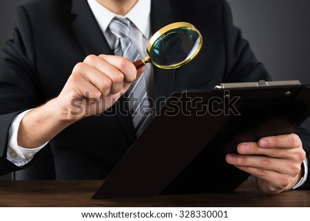 Close-up Of Businessperson Inspecting Document On Clipboard With Magnifying Glass - stock photo