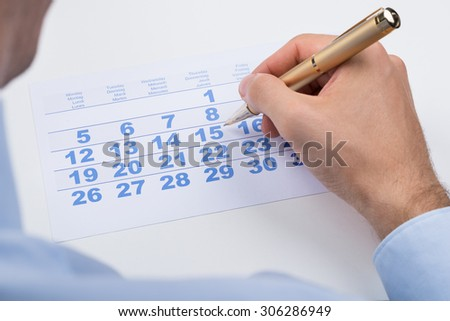 Close-up Of Businessperson Marking With Pen On Calendar