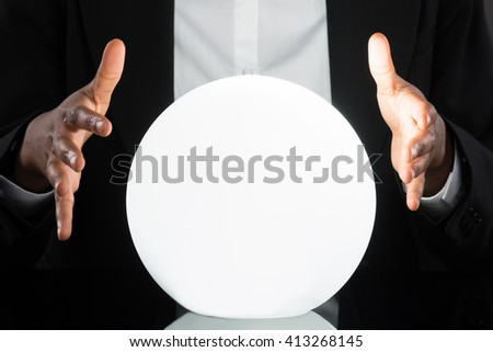 Close-up Of Businessperson Predicting Future With Crystal Ball On Desk - stock photo