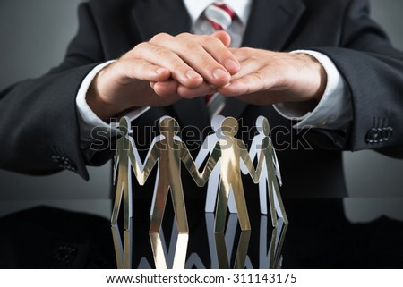 Close-up Of Businessperson Protecting Cutout Figures At Desk - stock photo