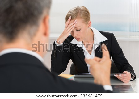 Close-up Of Businessperson Quarreling To Young Businesswoman At Desk - stock photo