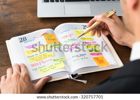 Close-up Of Businessperson Reading List Of Work In Diary - stock photo