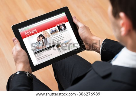 Close-up Of Businessperson Reading News Online On Digital Tablet - stock photo
