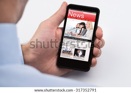 Close-up Of Businessperson Reading Online News On Mobile Phone - stock photo