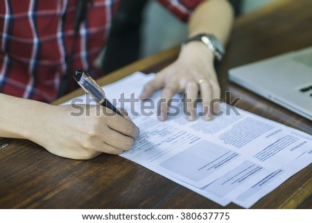 Close-up Of Businessperson Signing Contract,Man writing paper at the desk, man writing with pen and reading books at table,man Signing, Contract, Form. in office ,morning light ,selective focus. - stock photo