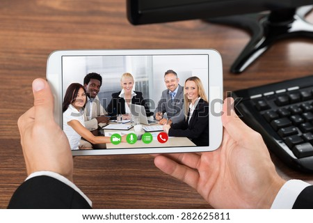 Close-up Of Businessperson Video Conferencing On Mobile Phone In Office - stock photo