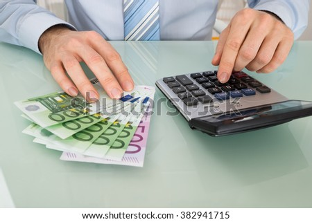 Close-up Of Businessperson With Banknote And Calculator At Desk
