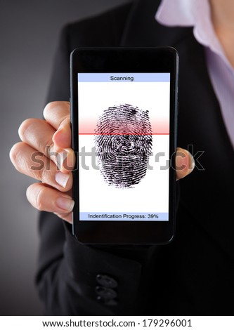 Close-up Of Businessperson With Cellphone Scanning A Fingerprint  - stock photo