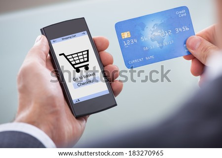 Close-up Of Businessperson With Mobile Phone Showing Online Shopping Application And Credit Card - stock photo