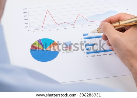 Close-up Of Businessperson With Pen Analyzing Statistic Chart On Paper - stock photo