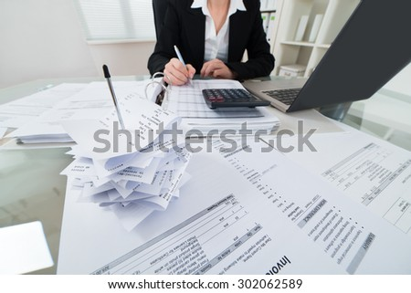 Close-up Of Businesswoman Calculating Tax With Calculator And Laptop At Desk - stock photo