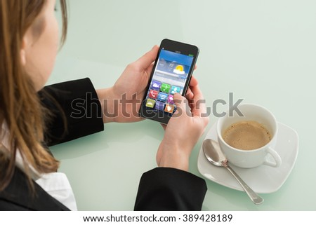 Close Up Of Businesswoman Checking Weather Forecast On Smartphone In Office - stock photo