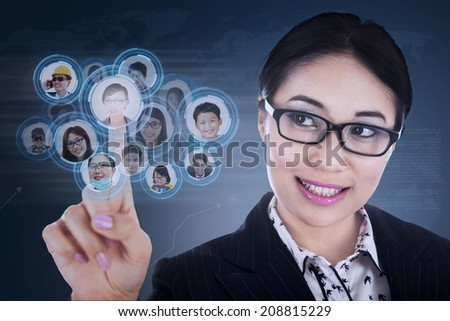 Close-up of businesswoman choosing few candidates on blue touchscreen - stock photo