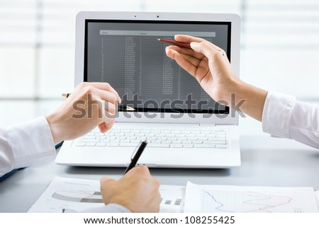 Close-up of businesswoman explaining a financial plan to colleagues at meeting - stock photo