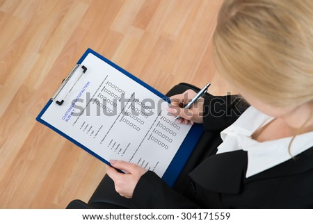 Close-up Of Businesswoman Filling Customer Survey Form On Clipboard With Pen - stock photo