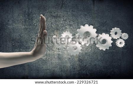 Close up of businesswoman hand and cogwheel mechanism - stock photo