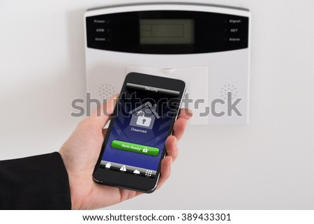 Close-up Of Businesswoman Hand Arming Security System Of Door - stock photo