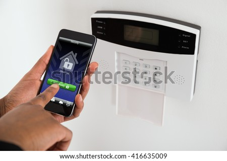 Close-up Of Businesswoman Hand Arming Security System Of Door