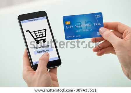 Close-up Of Businesswoman Hand Holding Credit Card And Mobile Phone