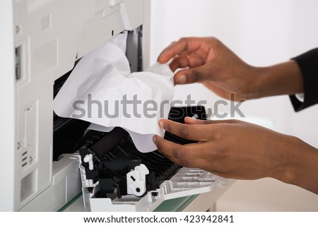 Close-up Of Businesswoman Hand Removing Paper Stucked In Printer At Office - stock photo