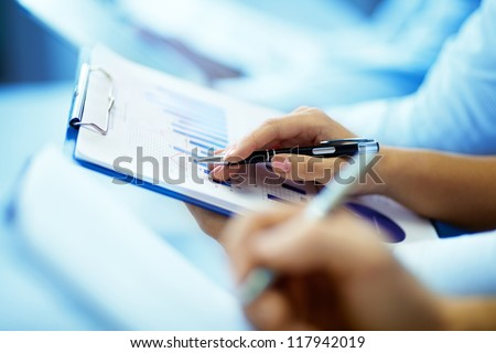 Close-up of businesswoman hand with document writing at lecture - stock photo