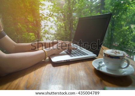 Close up of businesswoman hands typing a notebook with smart phone and coffee beside on a wooden table in the garden.Warm sunlight.Using smart phone.