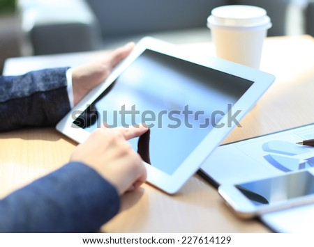 Close-up of businesswoman holding digital tablet and cup coffee  - stock photo