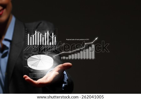 Close up of businesswoman holding graphs in hand - stock photo
