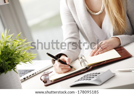 Close-up of businesswoman holding pen in hands and writing a note. - stock photo
