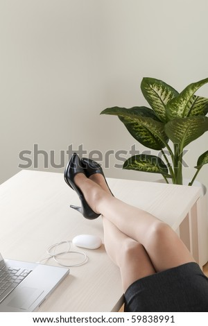 Close-up of businesswoman legs on the desk - stock photo