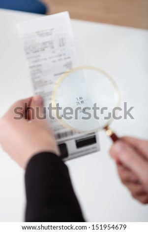 Close-up of businesswoman looking at check trough the loupe - stock photo