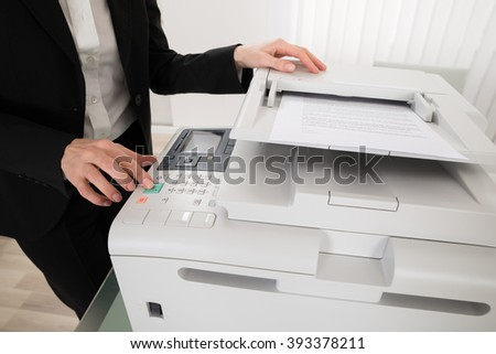 Close-up Of Businesswoman Pressing Printer's Button In Office