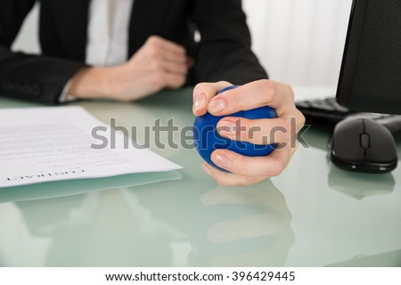 Close-up Of Businesswoman Pressing Stressball In Office