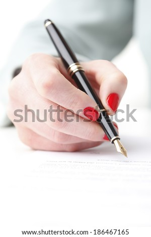 Close-up of businesswoman's hand fill form.